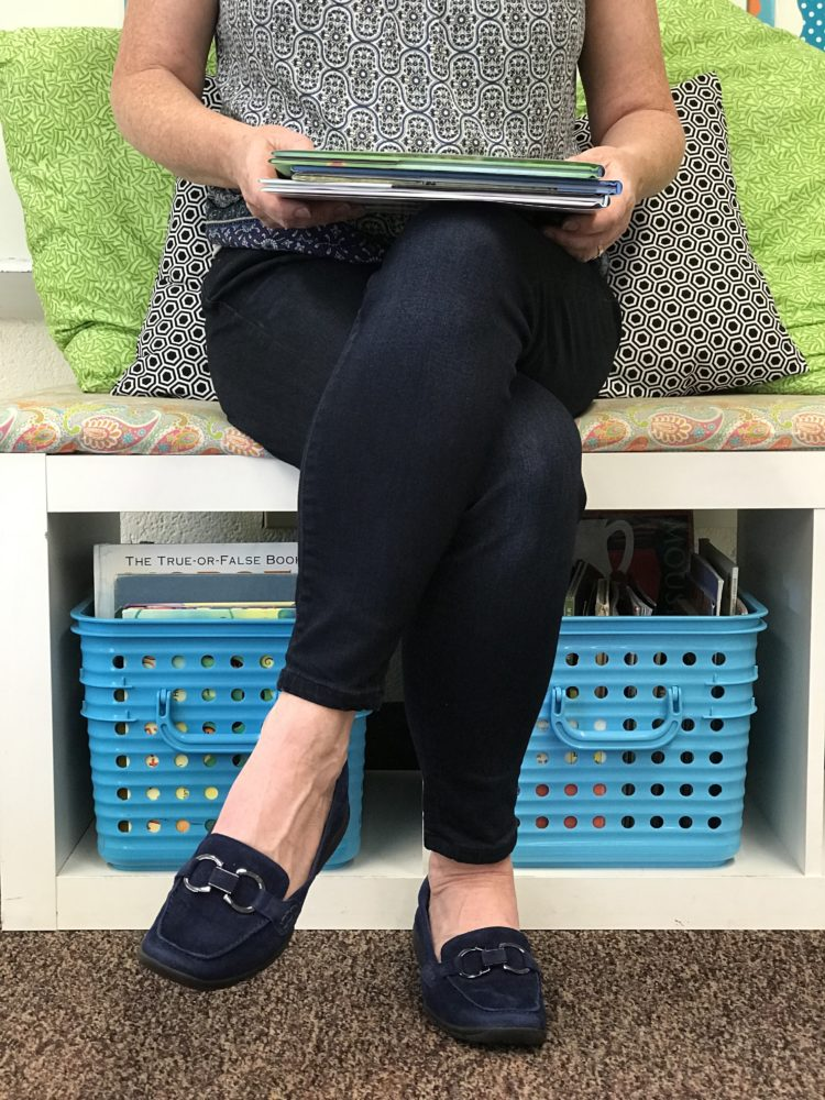 Teacher sitting with books wearing EasySpirit loafers.