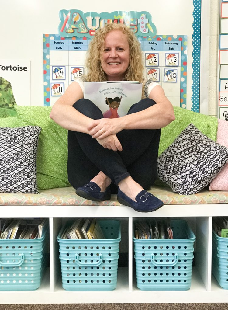 Teacher sitting holding books and wearing EasySpirit loafers.