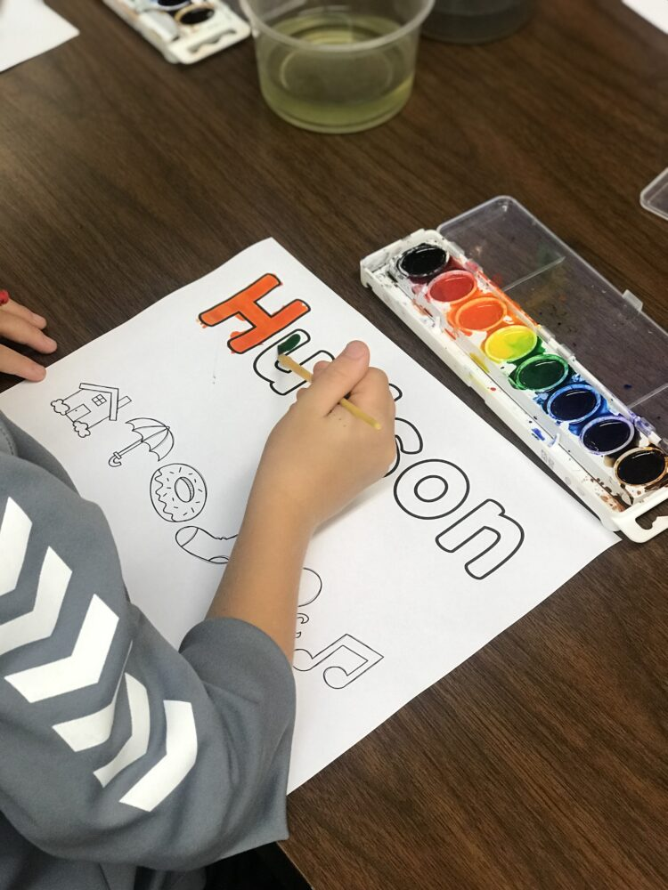 Student painting their name in letters and pictures with watercolor paints.