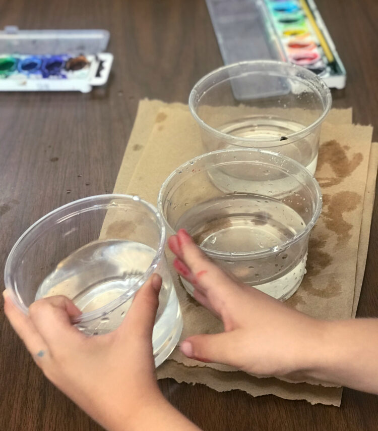 Preparing to paint with water cups.